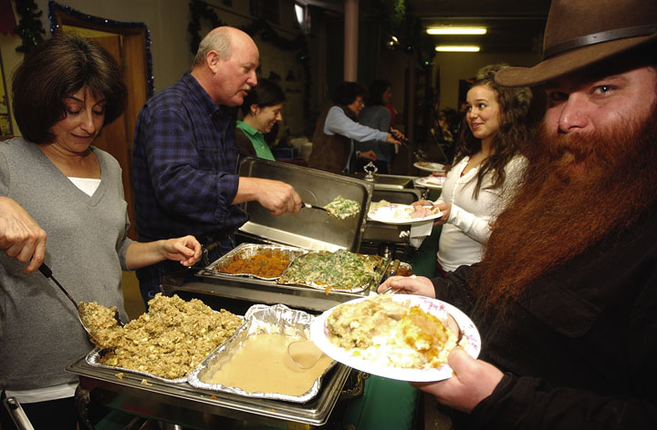 Christine Hands, left, with Alpenglow Properties, dishes stuffing while Jay Mogil loads his plate with gravy.