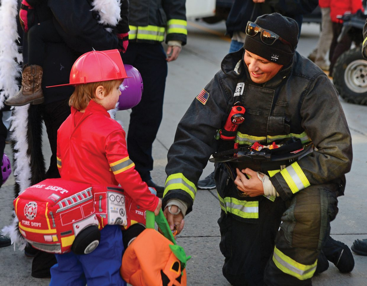 Steamboat Springs firefighter Isaiah Hartman hands out candy to Frankie Conley during Tuesday night's Halloween Stroll in downtown Steamboat Springs.