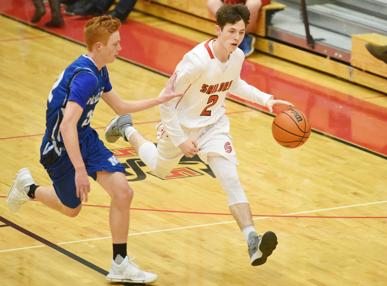 Connor Hansen pushes the ball up the floor Friday against Moffat County.