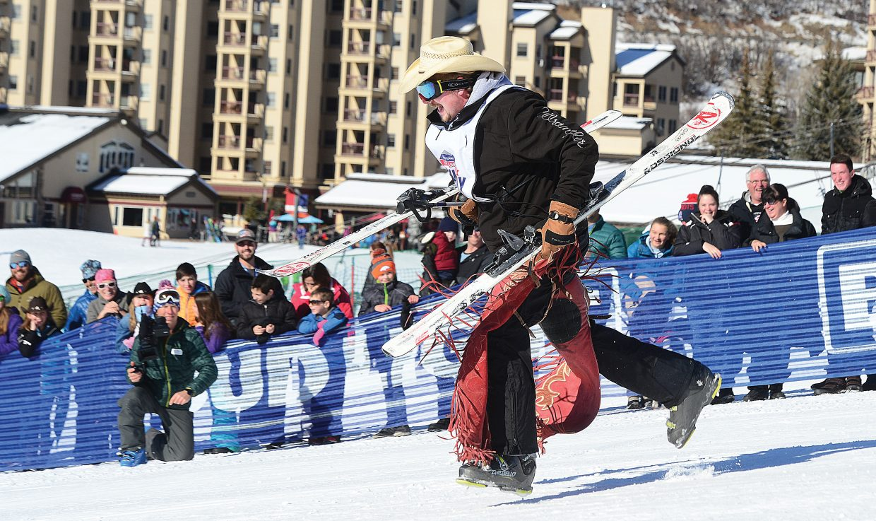 JW Miers, a saddle bronc rider from Wyoming, heads toward the finish line with skis in tow shortly after taking a spill in the middle of the 44th annual Cowboy Downhill at Steamboat Ski Area on Monday afternoon.