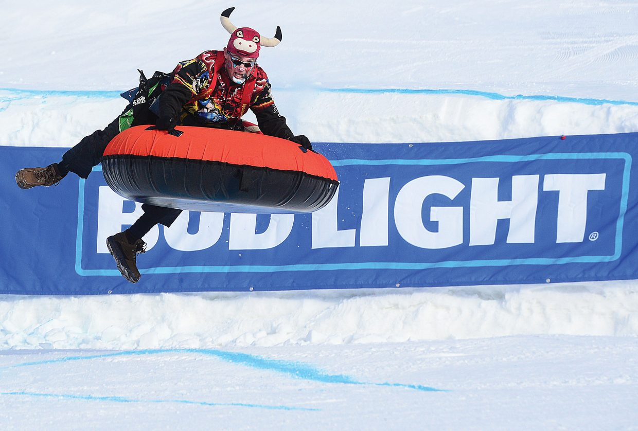 J.W. Winklepleck, a PRCA barrelman and rodeo clown, launches off the jump in the middle of the course at the 44th annual Cowboy Downhill at Steamboat Ski Area on Monday afternoon.
