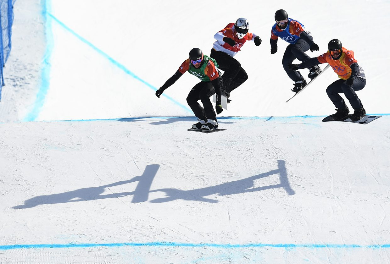 Mick Dierdorff, right, helps lead a pack of riders over a feature during the 2018 Winter Olympics snowboard cross event.