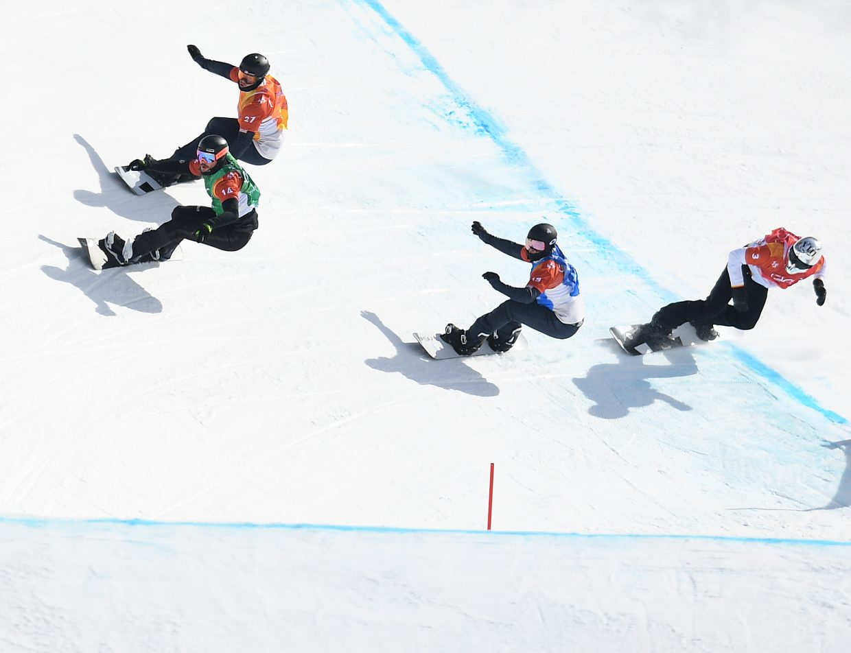 Mick Dierdorff, top, tries to keep pace with his first heat during the 2018 Winter Olympics snowboard cross event.