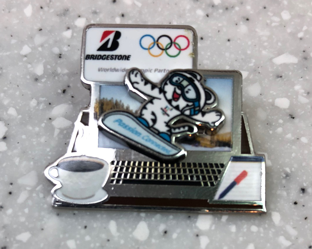 Bridgestone moving snowboarder Acquired: Trade with Korean volunteer. Thoughts: This is a highlight. The snowboarder actually moves, sliding left and right. It's the only pin I have with motion. I don't like that it's from a big corporate sponsor. It's weird the snowboarder is moving across the screen on a laptop, but, having spent so much of my Olympics working with a laptop and a notebook, it feels appropriate. Rating: 9