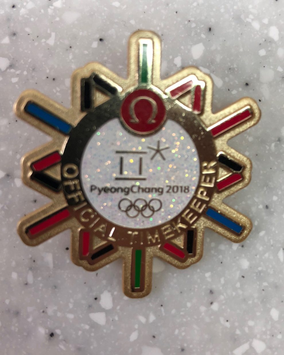 """Omega """"Official timekeeper"""" pin: Acquired: Ed Stoner, who got it from a pin trader. Thoughts: I don't love the corporate sponsor pins, but this is a sharp looking one. It was one of my first trades. Stoner — a Swift employee, previously the editor of the Vail Daily, a veteran of the 2014 Olympics and my main travel partner —traded a bunch of pins with a pin trader outside the MPC in the first few days of the Olympics. He ended up with a few doubles, and he swapped them to me to get some stock of Steamboat pins. Rating: 7"""
