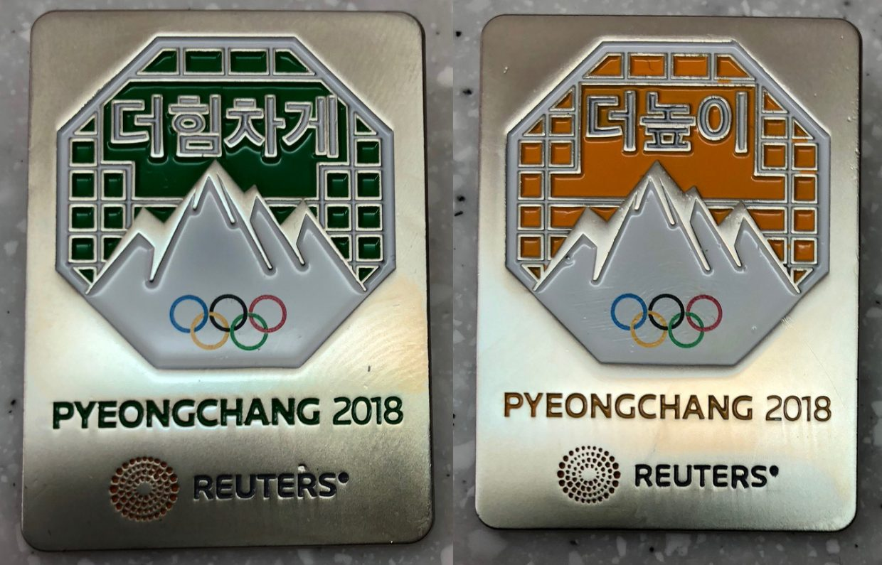 """Reuters (yellow and green): Acquired: At the Reuters office at MPC Thoughts: The Reuters guys just had a bowl of pins for people to grab from. They didn't seem to care one way or another, but I left them a Steamboat pin anyway. They had three colors, each with one of the Olympic words on the back, """"faster, stronger and higher."""" I got """"faster"""" and """"stronger."""" Rating: 7"""