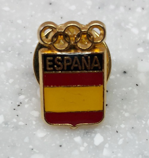 """Spanish flag pin Acquired: Team Spain photographer Thoughts: This pin came from one of my biggest days at the Olympics, the snowboarder cross event. The event started at 11 a.m. and ended at 3 p.m., or 11 p.m. in Steamboat, which would typically be too late to make the print edition of the newspaper. We had a local competing, however, in Mick Dierdorff, and we'd worked it out with the printing plant to publish at midnight (in Colorado) that one day.That's still cutting it close on my end, especially if Dierdorff goes for a medal. There are ceremonies and other interviews that really drag out the process. It took some athletes two hours to go from """"winning moment"""" to """"talking to American reporters.""""  I got to the course especially early and hiked up to find a good spot. I didn't think I had it at first, but another photographer, from the Associated Press, came along and together we climbed around on the side of a snowy hill until we found a vantage point we were happy with. (I just gave him a pin as he was a college buddy of John Russell's and said he'd once considered taking a job at the Steamboat Pilot & Today.) Eventually 20 other photographers followed us up there, including a hulking Spanish photographer. I asked him if he'd like to trade a pin. He dug into his jacket and came out with this. Rating: 6 for the pin, add two for it's connection to Dierdorff's fifth-place finish, one of the highlights of the Olympics. 8."""