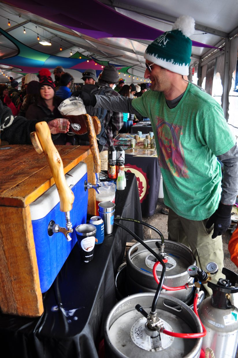 Josh Faulds, a controller at Crazy Mountain Brewing Co., pours a beer at WinterWonderGrass on Friday in Steamboat Springs.