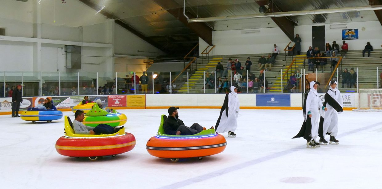 Employees of Resort Group participate in a relay race in Bumper Cars on Ice, with help from dancing penguins promoting the upcoming 14th Annual Penguin Plunge, during intermission at the Steamboat Wranglers Hockey game Friday night.