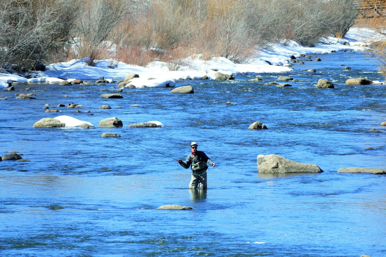 A man fly-fishes near the 5th Street Bridge along the Yampa River.