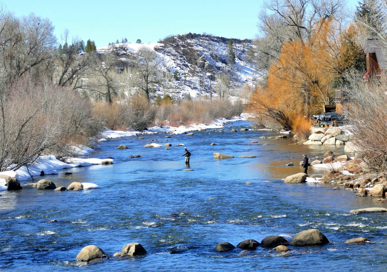 Two men fly-fish near the 5th Street Bridge along the Yampa River.