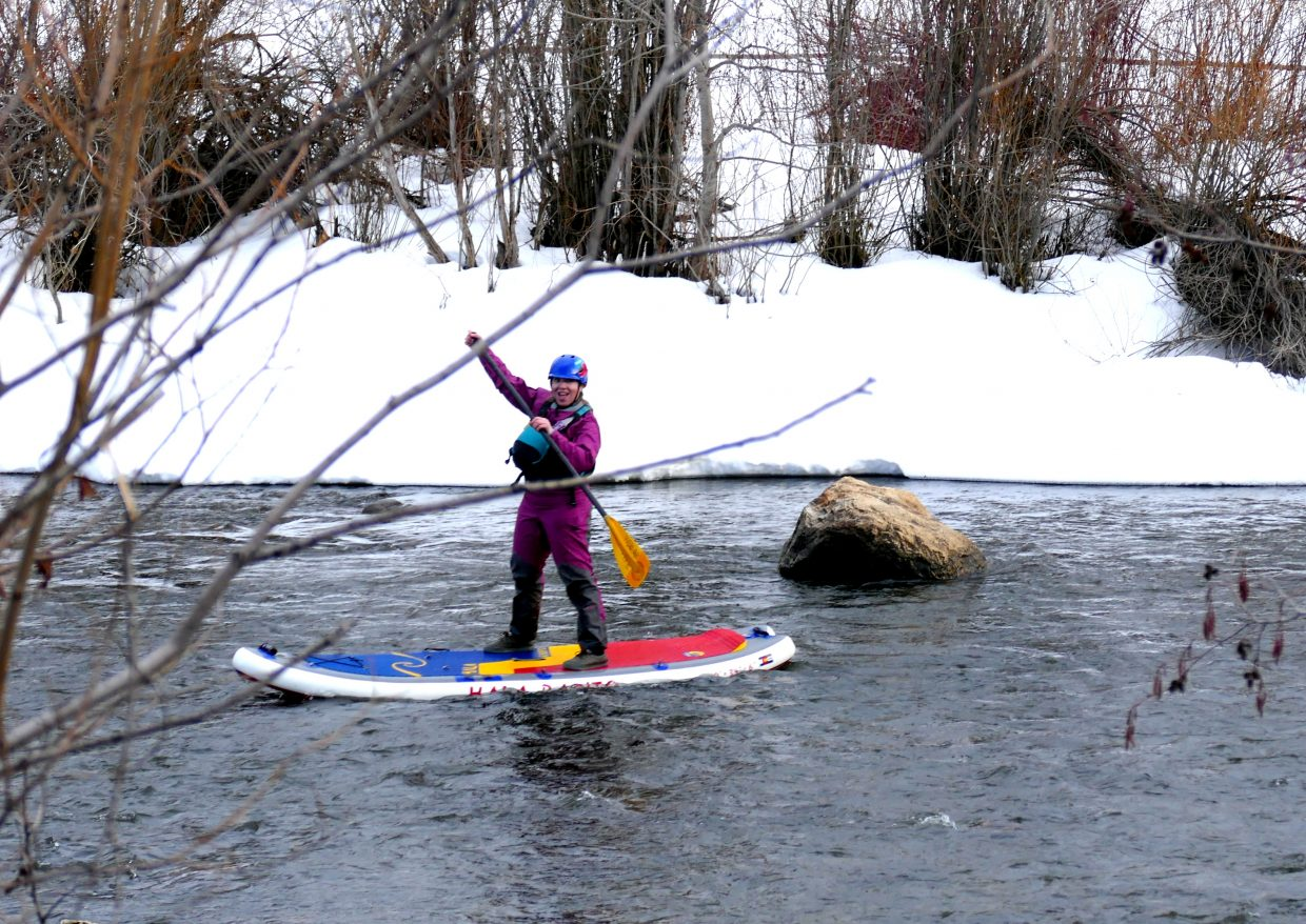 A paddleboarder makes her way down the Yampa River.