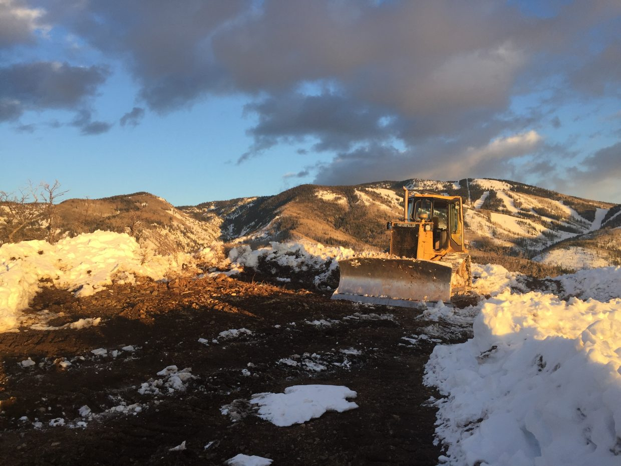 A snow plow on the top of Mount Werner works on cleaning up the snow.