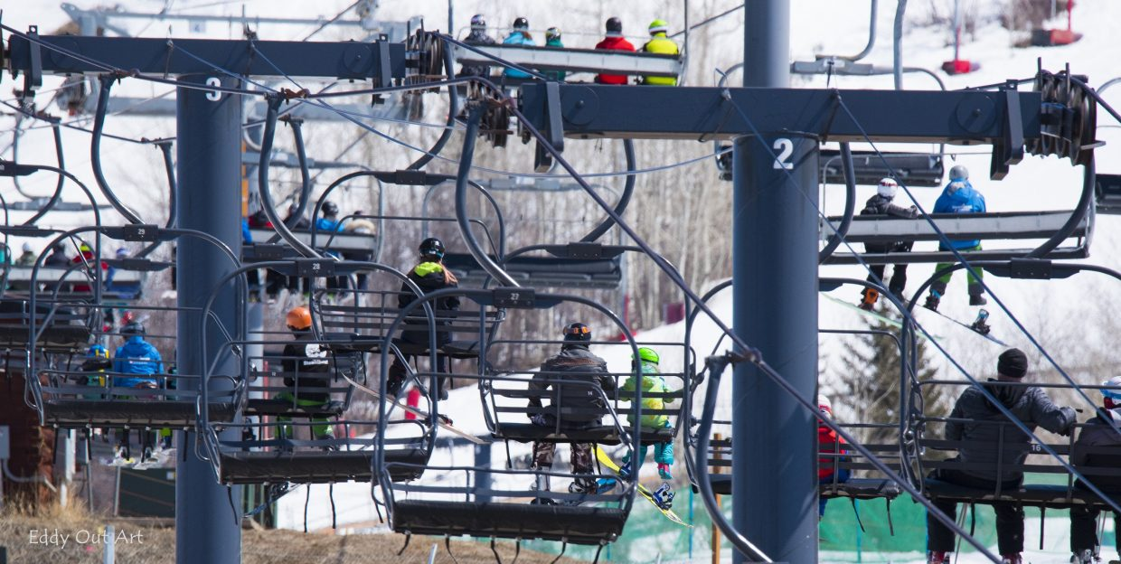 A shot of people piled onto a gondola headed up to ski.
