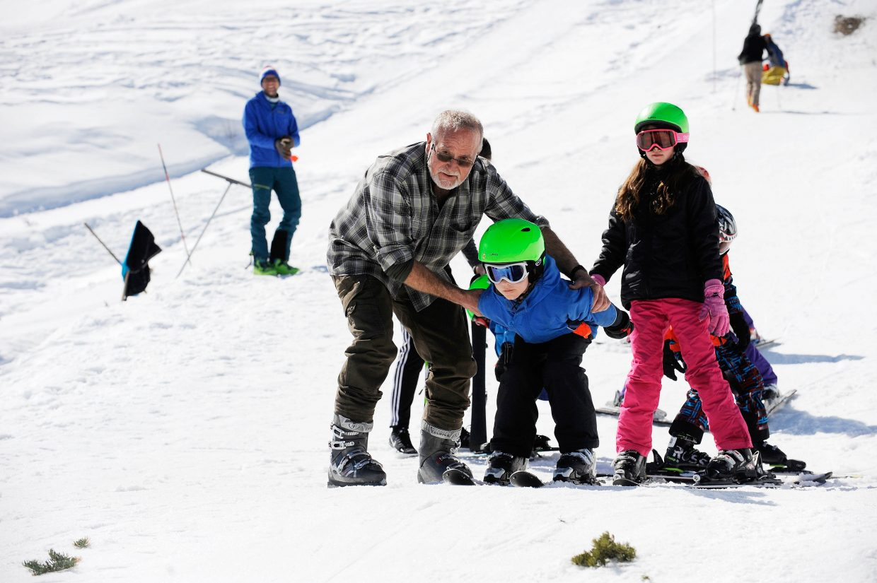 Scott Clayton coaches Jake Arnold on the ski jumps at Howelsen Hill during the final Free Ski Sundays event of the season. Jake, 9, was visiting Steamboat with his family from Houston, Texas.