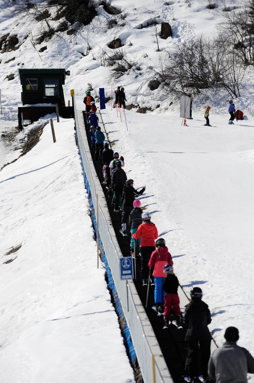 People ride the magic carpet during the final Free Ski Sundays event of the season at Howelsen Hill.