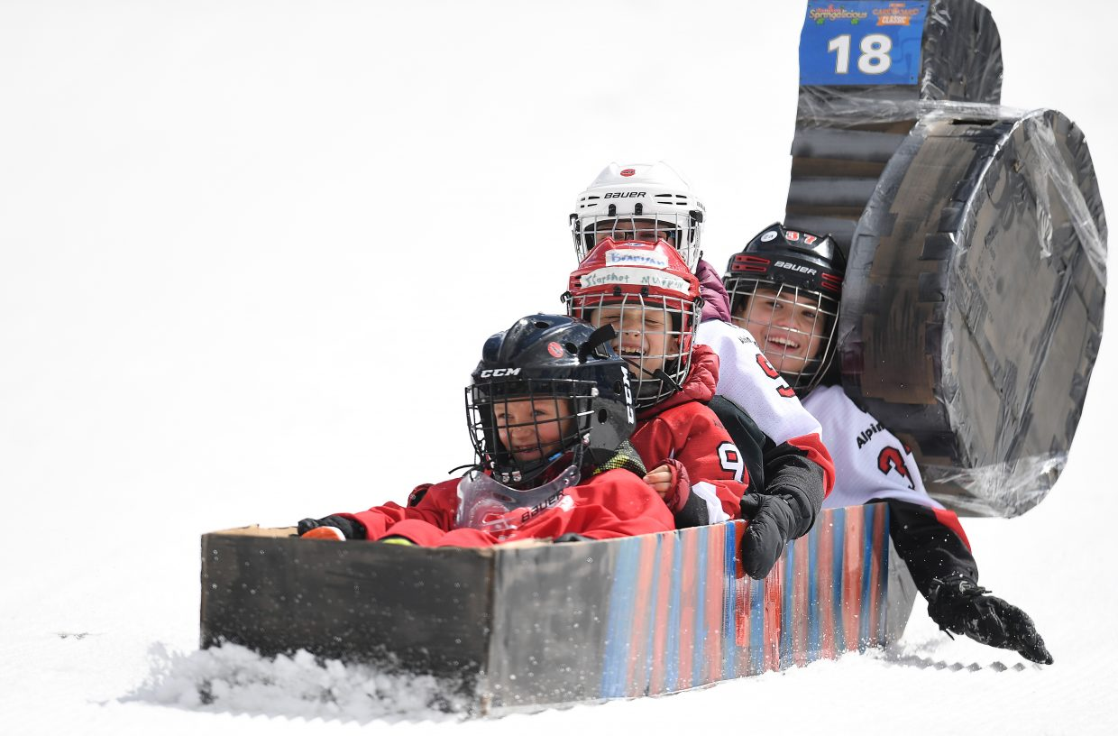 The team of Aiden Keane, Gavin Murphy, Branigan Murphy and Ridge Barnes ride their craft — a hockey stick and puck — down the Cardboard Classic course at Steamboat Ski Area.