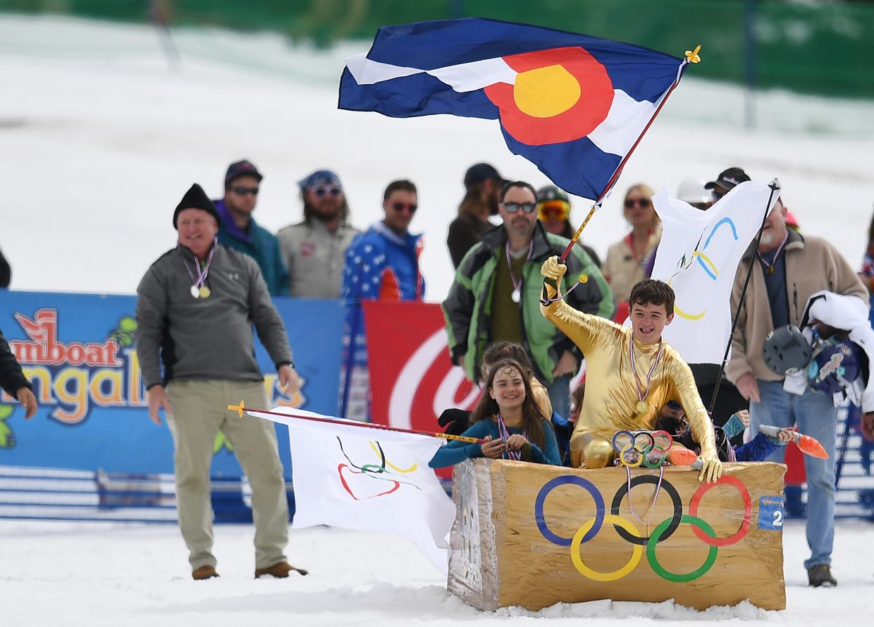 "Bradley Gampper waves the Colorado flag while he and his family start down the Cardboard Classic course in their craft, ""Going for Gold."""