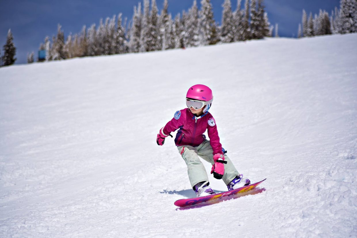 A little girl snowboards on the spring snow.