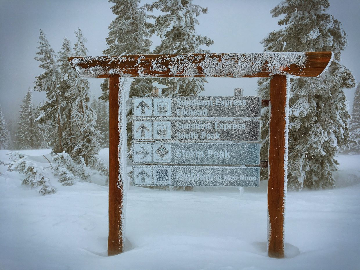 A ski trail sign covered in snow at the Steamboat Ski Area.