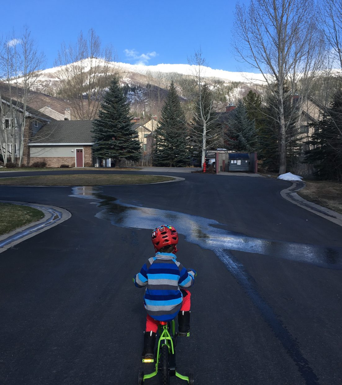 A little boy rides his bike as down in the valley shows signs of springs while the mountain holds onto winter.