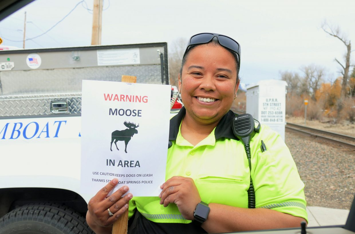 A community officer shows a sign warning people of the moose in the area.