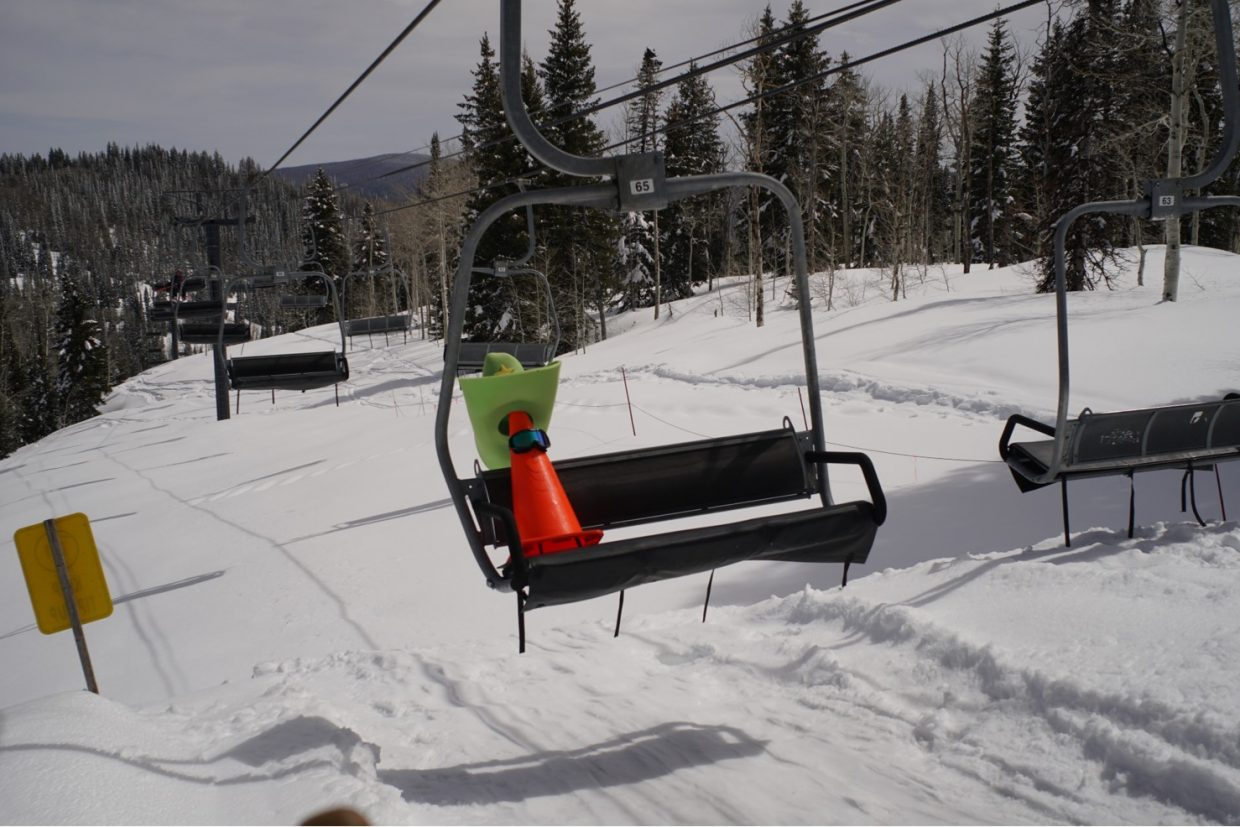 A cone dressed as a cowboy rides the ski lift at the Steamboat Ski Area.