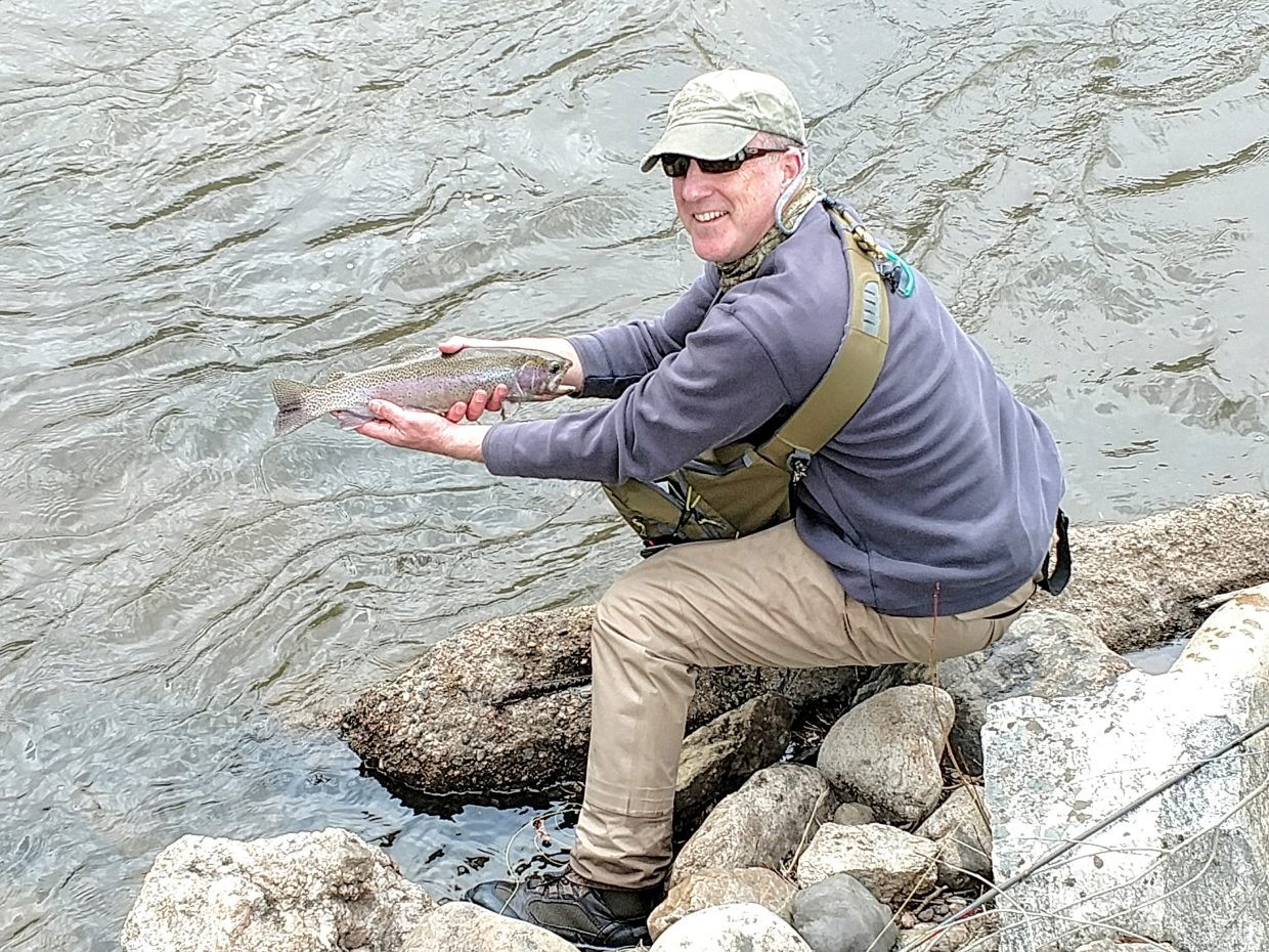 A man holds a fish along the Yampa River.