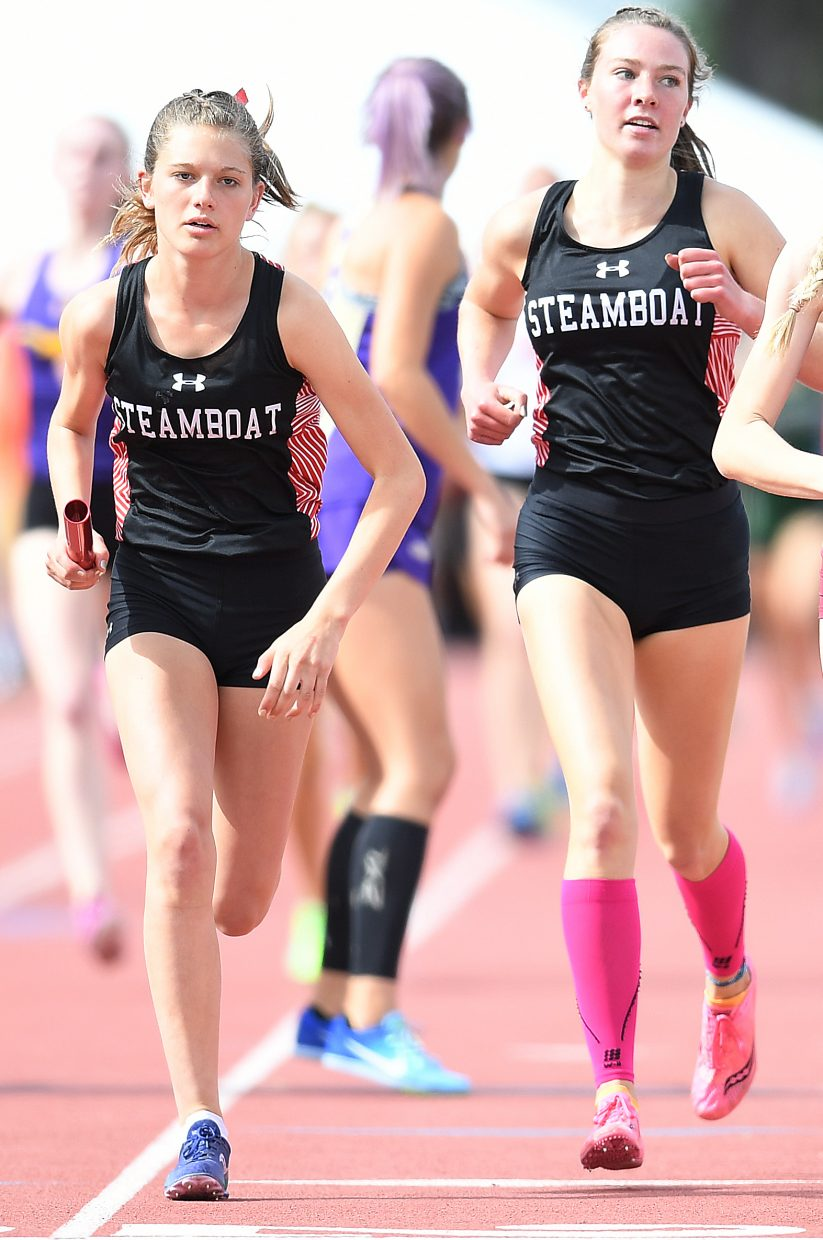 Isabelle Boniface takes off with the baton after Winter Boese finished the first leg of the girls 3A 3,200-meter relay on Thursday at the state track meet in Lakewood.