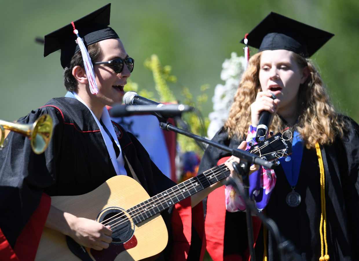 """Henry Tish, left, and Hannah Heil sing """"Flowers in the Sun,"""" on Saturday during the 2018 Steamboat Springs High School graduation ceremony, a song Tish wrote for the occasion."""