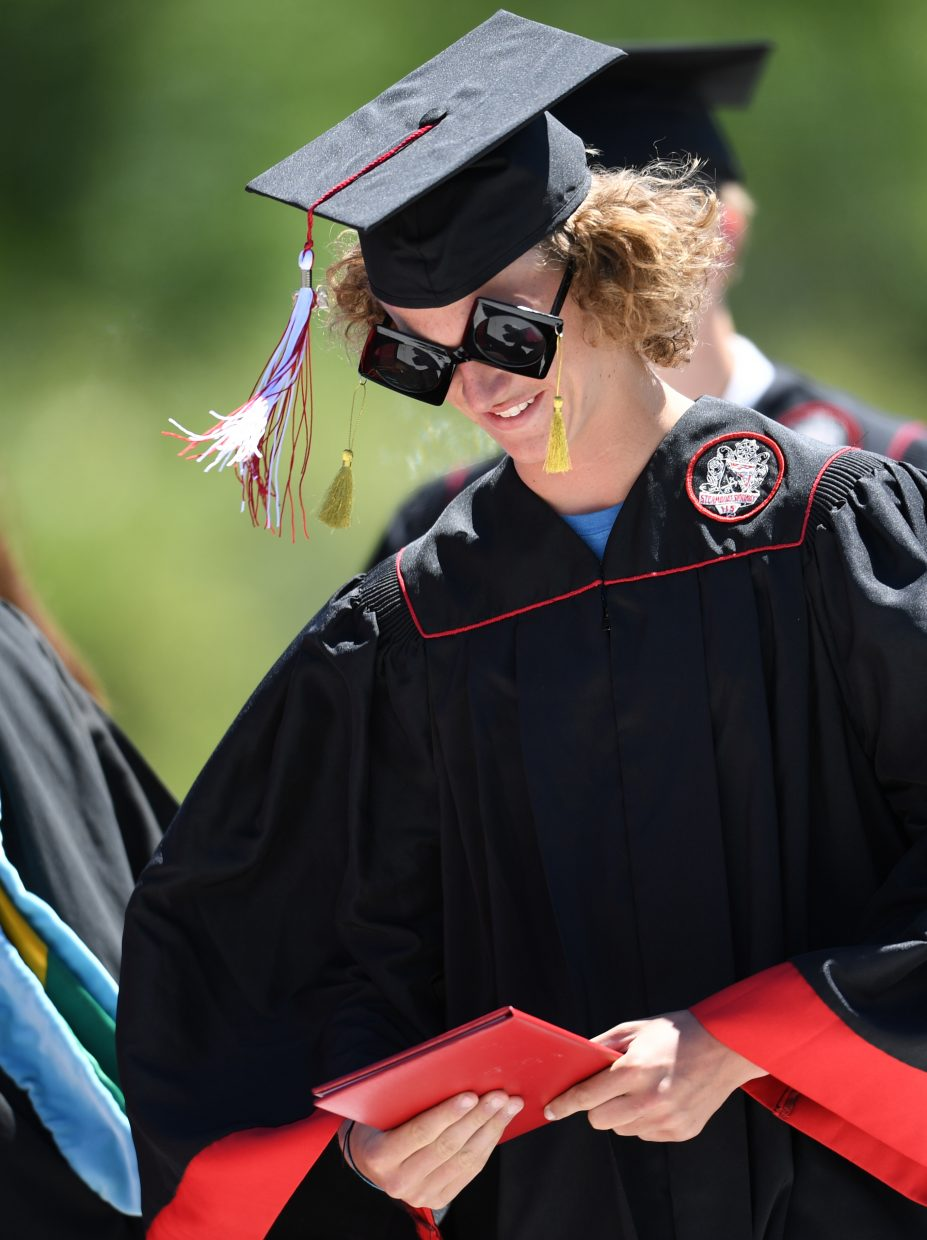 Cody Winters checks out his diploma Saturday through his special sunglasses.