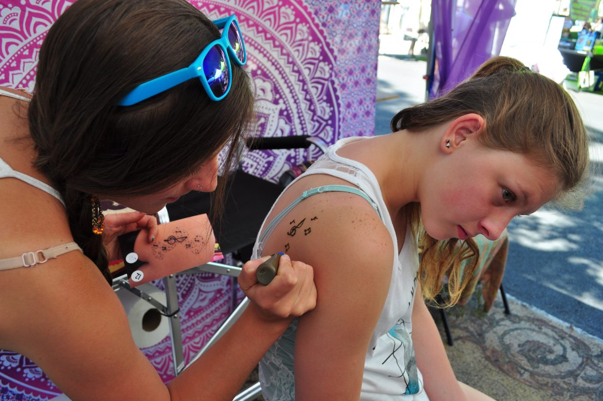 Katie Hoffmann works an a henna piece on Abby Crafe at the Mountain Girl Henna booth at the Farmers Market in Steambaot Springs.