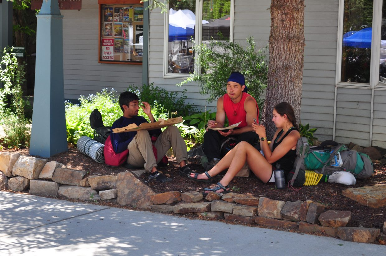 From left, Abhinav Jayakumar, of Indiana; Chase Kanekuni, of Hawaii; and Samantha Marks, of Indiana enjoy some shade and pizza from Clyde's Pies Wood-Fired Pizza at the Steamboat Farmers Market on Saturday.