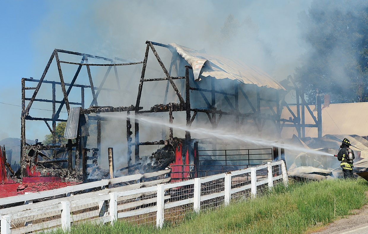 Steamboat Springs Fire Rescue's Scott Erickson extinguishes flames at a barn fire just off of Routt County Road 129. The blaze destroyed the iconic barn.