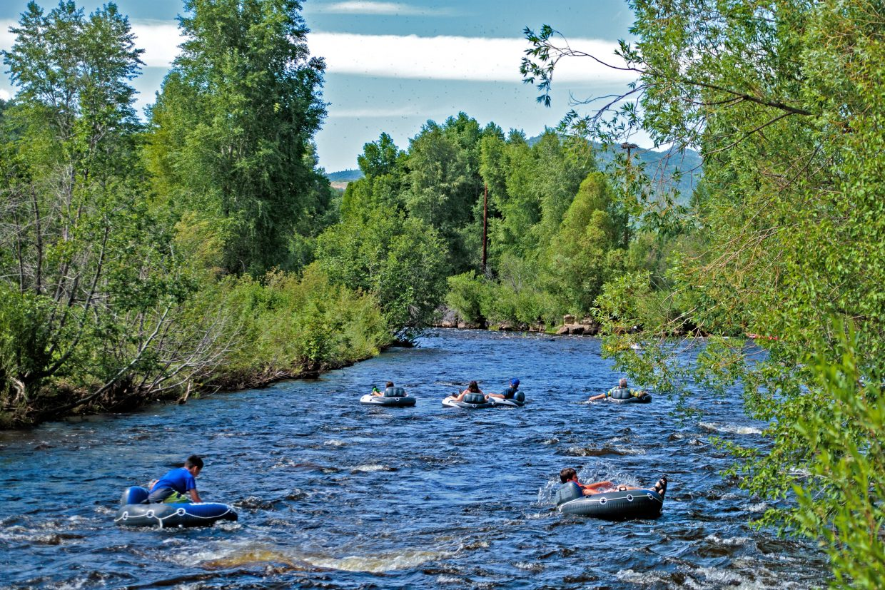 A trail of tubers float down the Yampa River.