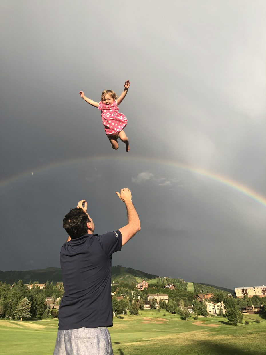Andy Jorgensen throws his daughter Kate playfully in the air over the rainbow.