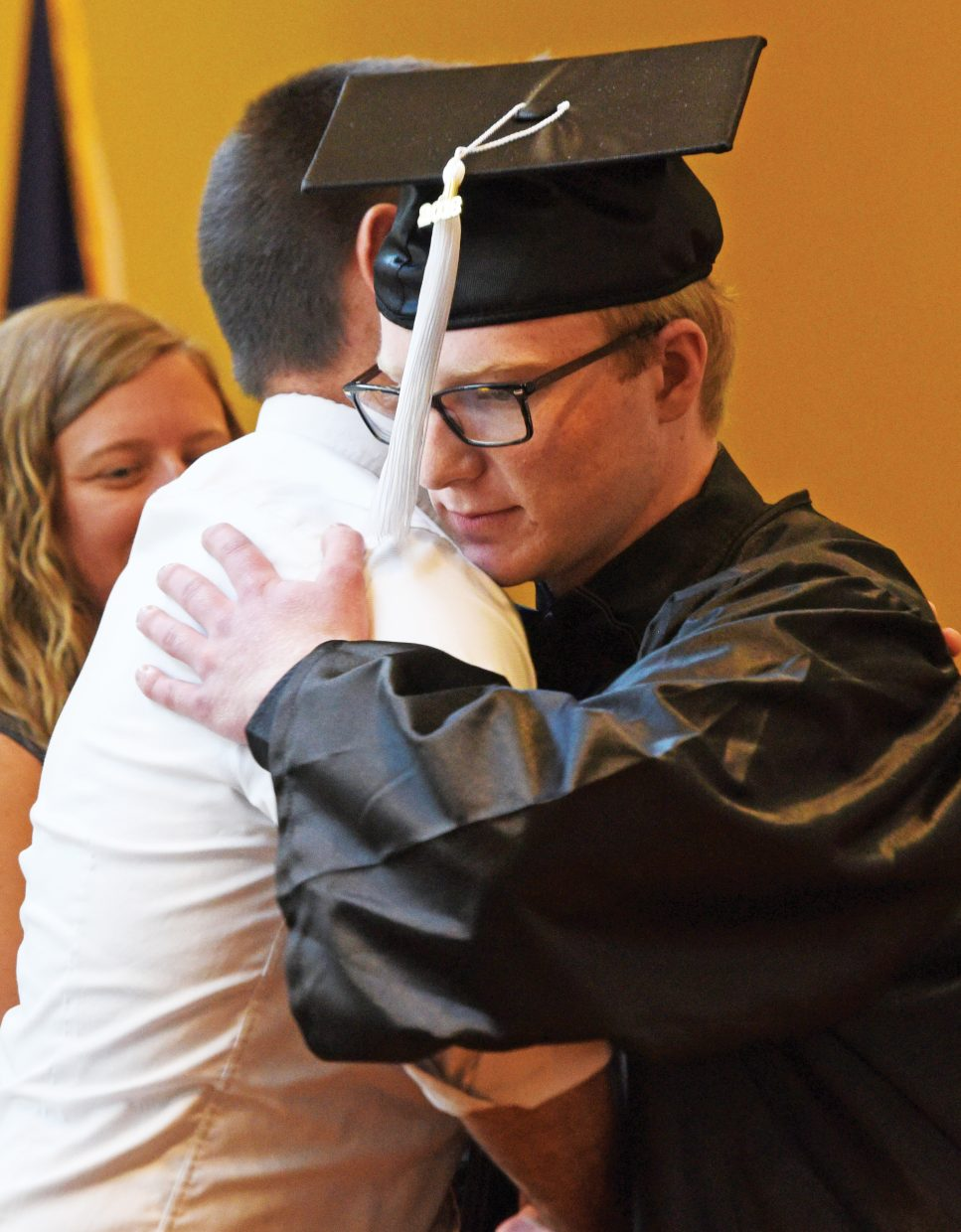 Heron Szyba gets a hug from a staff member at the Yampa Valley High School graduation Friday.