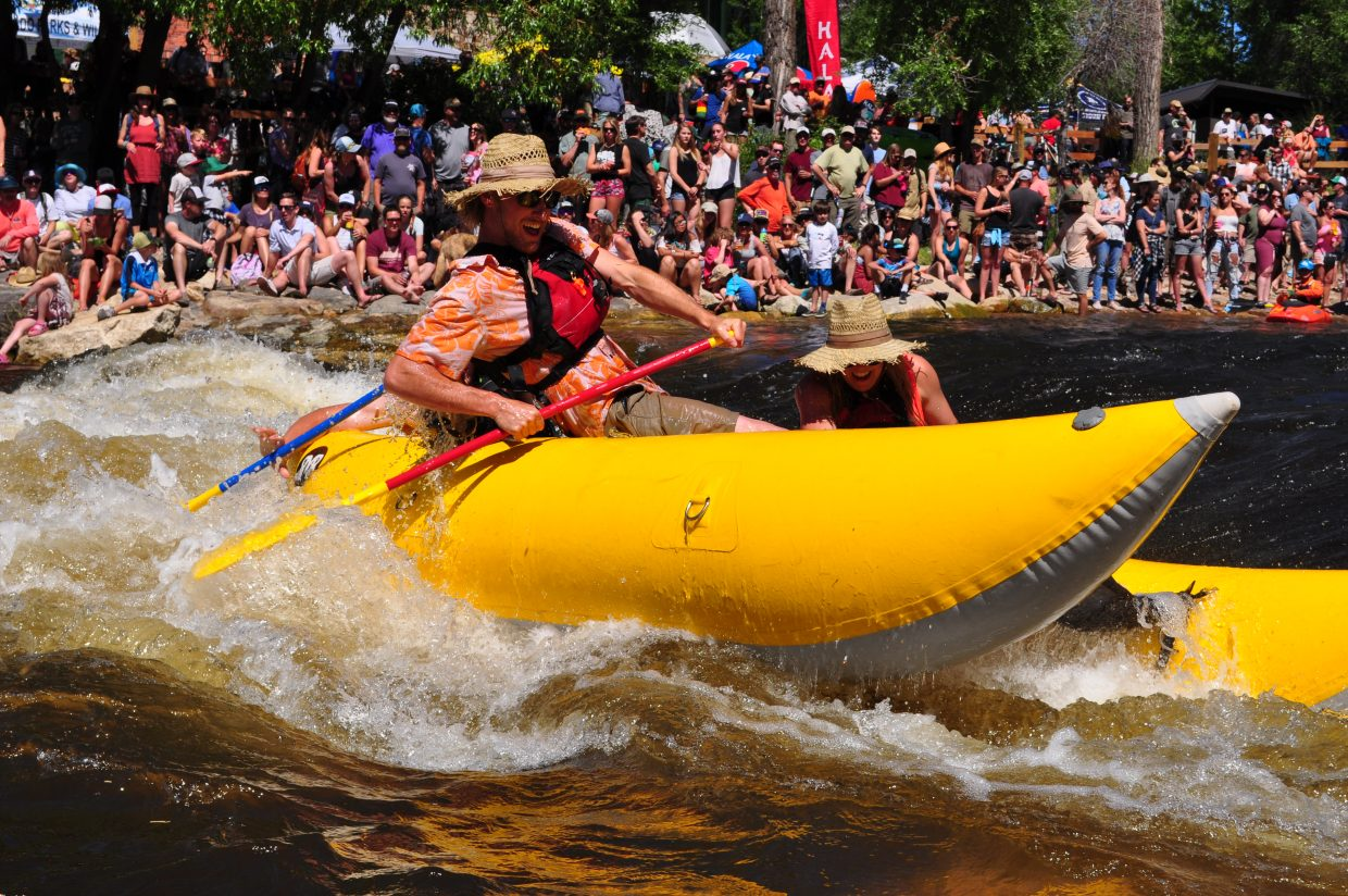 Rafters try their hand at surfing Charlie's Hole on the Yampa River by Bud Werner Memorial Library for the raft race and rodeo in Steamboat Springs on Saturday.