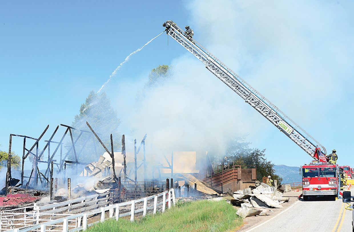 Firefighters use a ladder truck to battle a barn fire in North Routt County Monday morning. The blaze destroyed the historic barn on the Circle Bar Ranch.