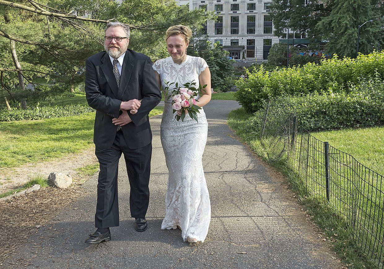 In an emotional climb up hill and without the use of his cane, Doug Zirkle, grabs onto his daughter, Rachel Zirkle's arm as they walk closer to the altar on Saturday, June 16, 2018 in Central Park in New York, New York. Doug Zirkle walked his daughter up hill and down the aisle without the use of his cane, nearly a year after a horrific car accident.