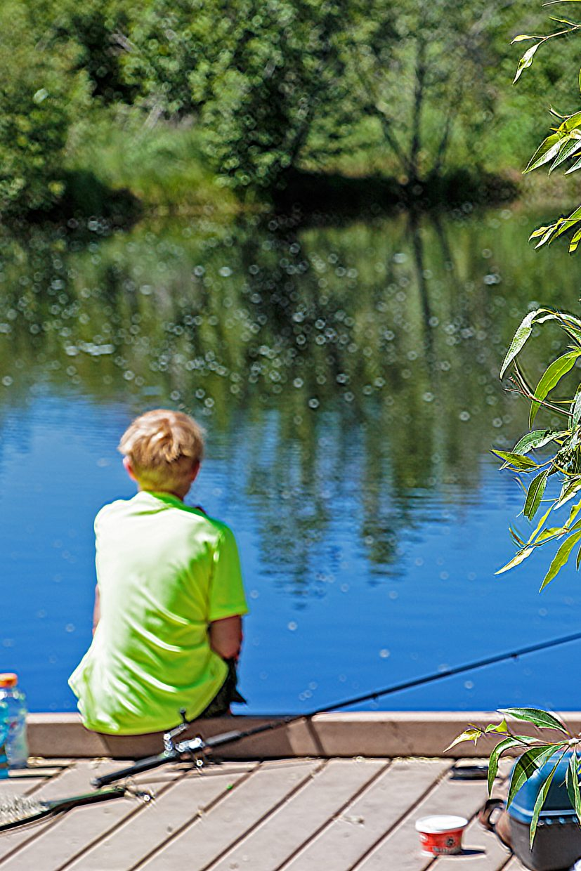 A little boy fishes at the fishing hole at Fletcher's Pond.