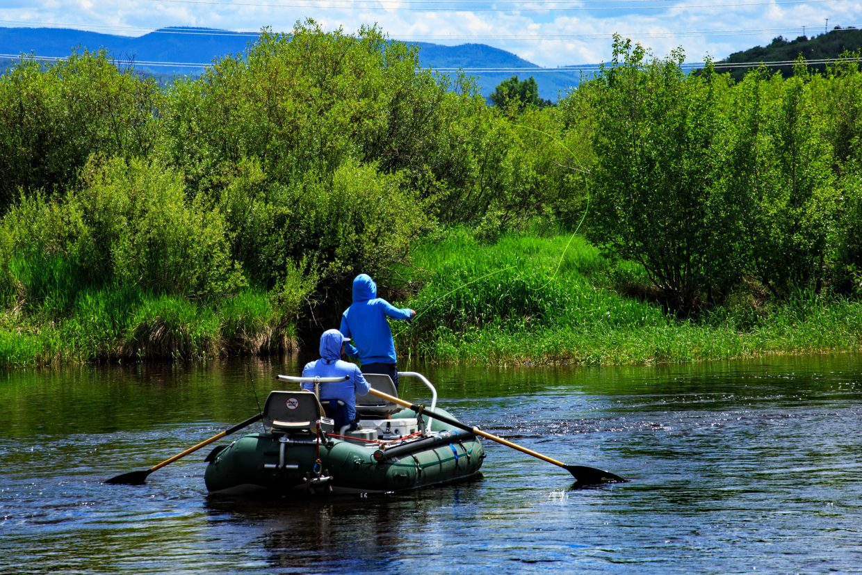 Two people fish on a float down the Yampa River. Please remember the river is officially closed to all recreational use until further notice.