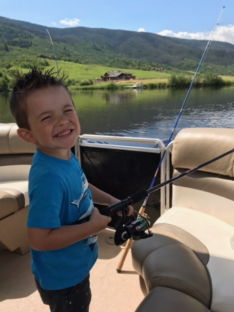 A little boy smiles as he casts his line to fish.