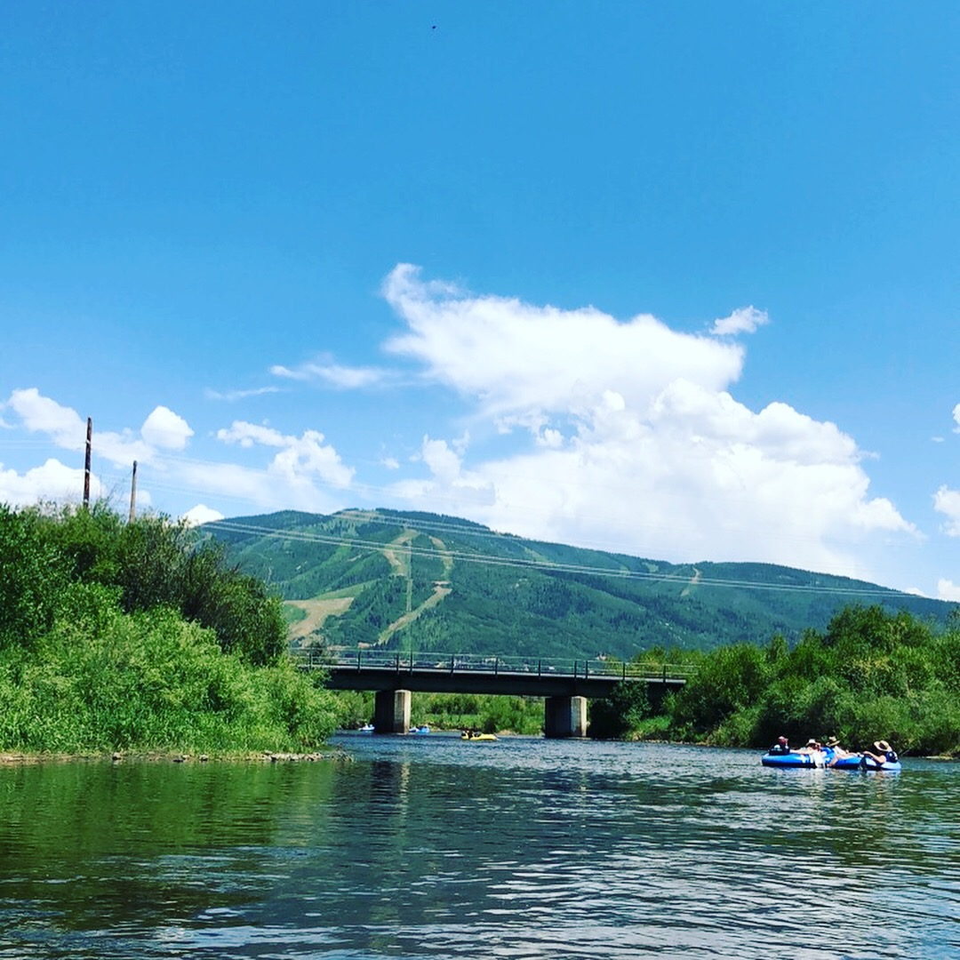 Deep green vegetation is seen as people tube down the Yampa River.