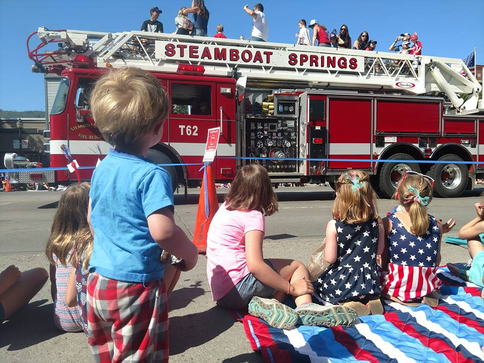 Kids wave as a fire truck passes during the Steamboat Springs Fourth of July parade.