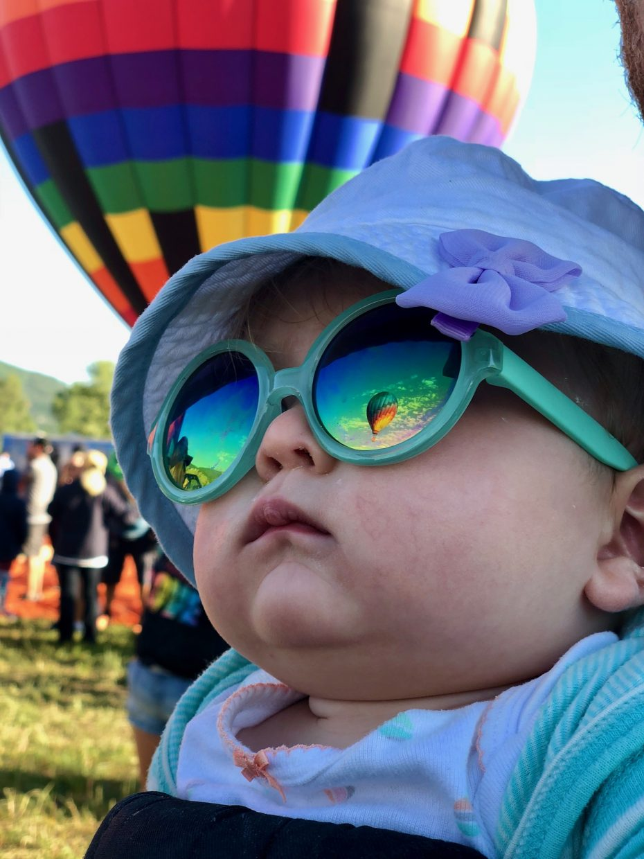 Balloons during the Hot Air Balloon Rodeo can be seen in a little girl's sunglasses as she watches at Bald Eagle Lake.