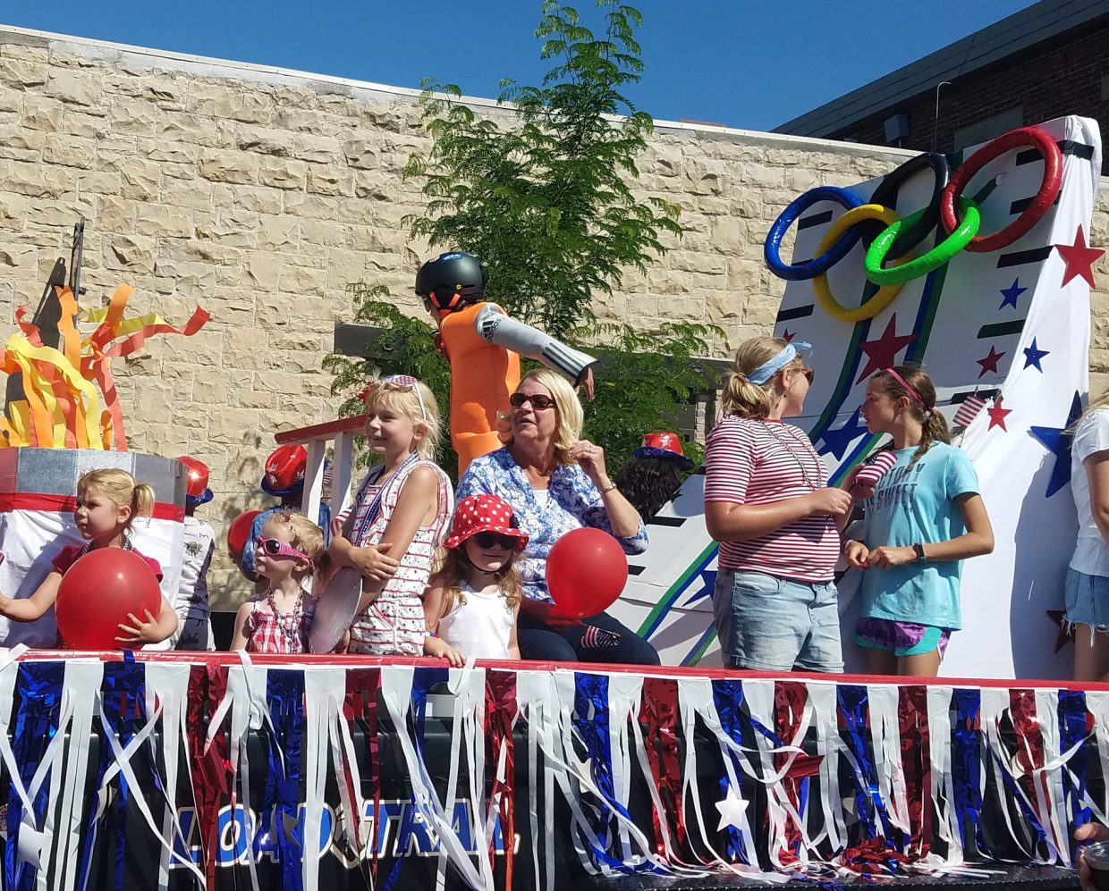 Women and children ride a float modeled after theme of this year's Fourth of July parade, Red, White and Gold: Celebrating Our Olympians.