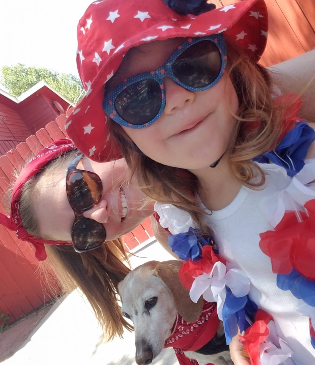 Two girls smile in a selfie before the start of the Fourth of July parade.