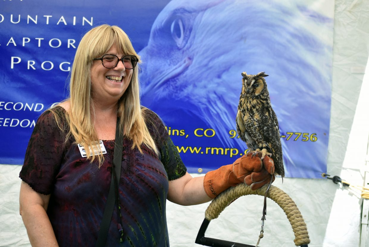 Christine Chapman, a volunteer at Rocky Mountain Raptors holds a long-eared owl at the organization's booth at Art in the Park in Steamboat Springs on Sunday.