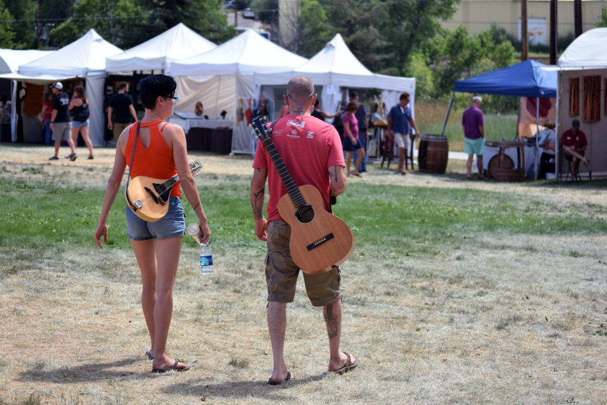 Callie Bradley, left and Ken Spencer walk with instruments in tow through Art in the Park in Steamboat Springs on Sunday.